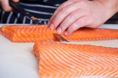 Pescados de los salmones del corte del cocinero Imagen de archivo