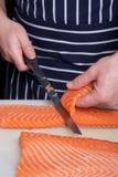 Pescados de los salmones del corte del cocinero Foto de archivo libre de regalías
