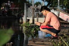 Pescados del lanzamiento de los budistas de nuevo al río Fotos de archivo