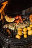 Pescados deliciosos de la trucha arco iris con los tomates, las patatas y el limón cocinando en parrilla llameante caliente Barba fotografía de archivo