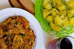 Pescados fritos almuerzo, patatas hervidas y vino rojo Foto de archivo
