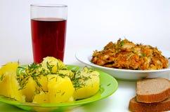 Pescados fritos almuerzo, patatas hervidas y vino rojo Imagen de archivo