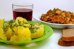 Pescados fritos almuerzo, patatas hervidas y vino rojo Fotografía de archivo libre de regalías