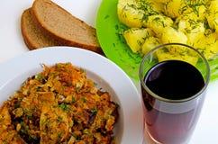 Pescados fritos almuerzo, patatas hervidas y vino rojo Fotografía de archivo