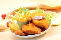 Pescados fritos empanados con las fritadas de la patata y la salsa de tomate de tomate con el tomate de cereza del limón Fotos de archivo