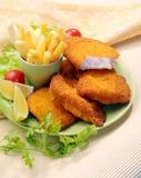 Pescados fritos empanados con las fritadas de la patata y la salsa de tomate de tomate con el tomate de cereza del limón Imagenes de archivo