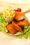 Pescados fritos empanados con las fritadas de la patata y la salsa de tomate de tomate con el tomate de cereza del limón Fotografía de archivo libre de regalías