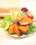 Pescados fritos empanados con las fritadas de la patata y la salsa de tomate de tomate con el tomate de cereza del limón Fotos de archivo libres de regalías