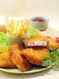 Pescados fritos empanados con las fritadas de la patata y la salsa de tomate de tomate con el tomate de cereza del limón Foto de archivo