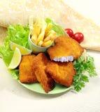 Pescados fritos empanados con las fritadas de la patata y la salsa de tomate de tomate con el tomate de cereza del limón Imágenes de archivo libres de regalías