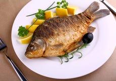 Pescados fritos en la placa blanca con el cuchillo y la bifurcación imagen de archivo libre de regalías