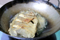 Pescados fritos en un sartén en la cocina fotografía de archivo