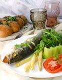 Pescados fritos (lubina) con el espárrago, el tallo del apio, el arugula y el tomate Fotografía de archivo