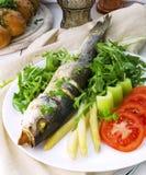 Pescados fritos (lubina) con el espárrago, el tallo del apio, el arugula y el tomate Foto de archivo