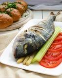 Pescados fritos (Dorada) con el espárrago, tallo del apio,   Fotografía de archivo