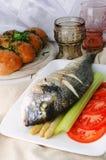 Pescados fritos (Dorada) con el espárrago, el tallo del apio, el berro y el tomate Foto de archivo
