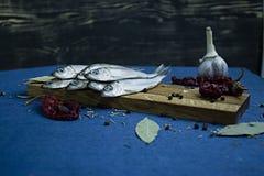 Pescados herringSalted picantes en un soporte de madera imagenes de archivo