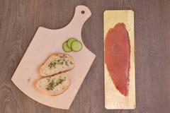 Pescados, pan y pepino en rebanadas en tabla de cortar fotografía de archivo