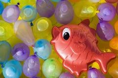Pescados rojos del juguete entre los impulsos coloreados Foto de archivo libre de regalías