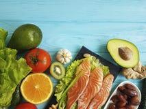 Pescados rojos Omega 3, nueces frescas en de madera azul, comida sana del aguacate de la composición foto de archivo libre de regalías