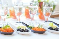 Pescados rojos y negros del caviar en las cucharas blancas, negras Fotografía de archivo libre de regalías