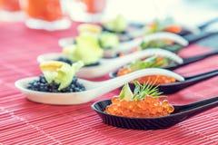 Pescados rojos y negros del caviar en las cucharas blancas, negras Fotos de archivo