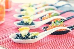 Pescados rojos y negros del caviar en las cucharas blancas, negras Imágenes de archivo libres de regalías