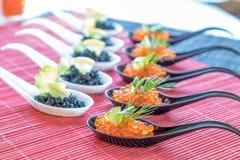 Pescados rojos y negros del caviar en las cucharas blancas, negras Foto de archivo libre de regalías