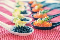 Pescados rojos y negros del caviar en las cucharas blancas, negras Imagen de archivo libre de regalías
