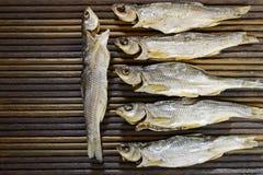 Pescados secados en una tabla texturizada Fotografía de archivo