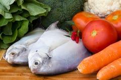 Pescados sin procesar con las verduras frescas Foto de archivo libre de regalías