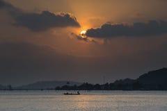 Pescando al crepuscolo nell'ambito di un'alba arancio incredibile Immagine Stock Libera da Diritti