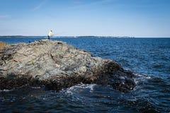 Pescando da una scogliera nell'Oceano Atlantico fotografia stock
