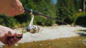 Pescando en un pequeño río de la montaña, en el marco de la mano de un pescador con una caña de pescar almacen de metraje de vídeo