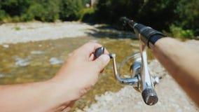 Pescando en un pequeño río de la montaña, en el marco de la mano de un pescador con una caña de pescar metrajes