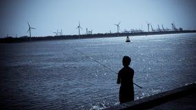 Pescando nel porto Immagini Stock