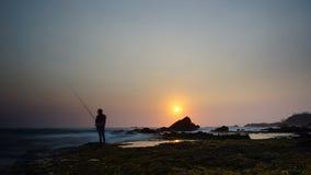 Pescando nell'ambito del tramonto Immagini Stock