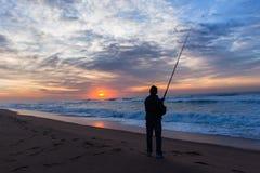 Pescando o nascer do sol mostrado em silhueta do oceano da praia Foto de Stock