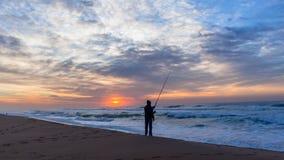 Pescando o nascer do sol mostrado em silhueta do oceano da praia Fotos de Stock