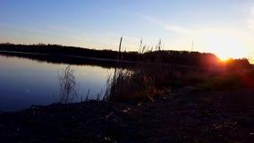 Pescando o ponto no nascer do sol do amanhecer ao lado do lago O melhores lugar e hora secretos pescar em Dawn With Calm Water