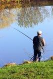 Pescando o sénior no lago Foto de Stock