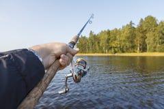 Pescando su un lago Canna da pesca con una bobina a disposizione Immagini Stock Libere da Diritti