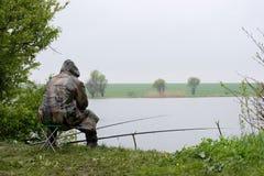 Pescando su un lago in maltempo Fotografia Stock