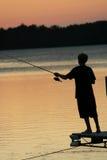Pescando sul lago al tramonto Immagini Stock