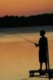 Pescando sul lago al tramonto Immagine Stock