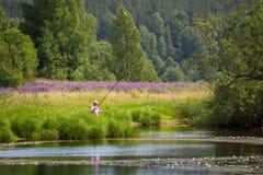 Pescando sul lago con i gigli nella posizione rurale Immagini Stock