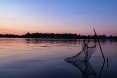 Pescar no banco de rio é uma grade para peixes na água no fundo de um bom por do sol fotografia de stock royalty free