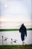 Pescatore al bordo del lago che esamina le canne da pesca immagini stock