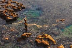 Pescatore al litorale di mare con rete da pesca Fotografia Stock Libera da Diritti