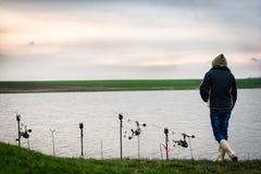 Pescatore al tramonto al bordo del lago vicino alle canne da pesca fotografia stock
